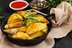 Fried potatoes with fresh rosemary in cast-iron pan. Rustic style Royalty Free Stock Photography