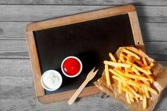 Fried Potatoes Fries och såser ovanför den svart tavlan royaltyfri foto