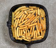 Fried potatoes in frying pan. On grey table, top view Stock Photos