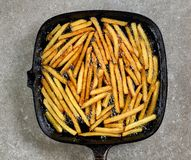 Fried potatoes in frying pan. On grey table, top view Stock Photo