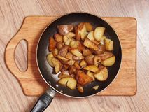 Fried potatoes in a frying pan. Potatoes fried in a rustic manner on a cutting board in an old cast-iron frying pan Stock Images