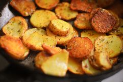 Fried potatoes in a frying pan sprinkled with seasoning. Royalty Free Stock Photos
