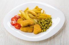 Fried potatoes, green peas, tomato cherry, chicken nuggets in pl. Fried potatoes, green peas, tomato cherry, chicken nuggets in white plate royalty free stock photos