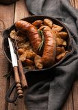 Fried potatoes and grilled sausages in pan with fork, knife near grey napkin royalty free stock photography