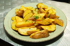 Fried potatoes with herbs. In a plate on the bar Stock Photo