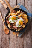 Fried potatoes with meat, bacon and eggs in a pan. vertical top Stock Photos