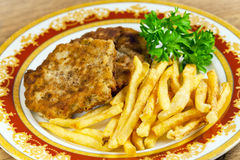 Fried potatoes with meat cutlet. And parsley on a plate - fastfood stock photo