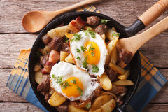 Fried potatoes with meat and eggs in a pan closeup. horizontal royalty free stock photography