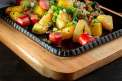 Fried potatoes with mushroom and sausage in cast iron frying pan. royalty free stock photos