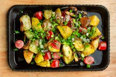 Fried potatoes with mushroom and sausage in cast iron frying pan. stock photos