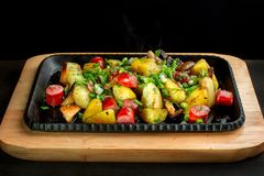 Fried potatoes with mushroom and sausage in cast iron frying pan. royalty free stock image