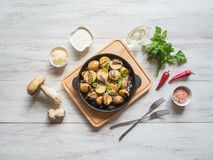 Fried potatoes with penny bun on a cast iron pan. Rustic cusine. Fried potatoes with penny bun on a cast iron pan. Rustic cusine stock photo