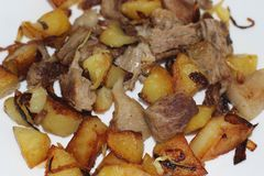 Fried potatoes and pork on white plate stock photos