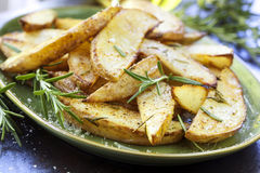 Fried Potatoes with Rosemary. And sea salt flakes, on a green plate.  Oven baked wedges Stock Image