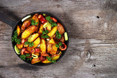 Fried potatoes with sausages, onion rings and green parsley. Mea. L served in old cast iron frying pan on wooden table Royalty Free Stock Photography