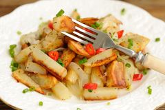 Fried potatoes with scallion and chili in white plate with fork Royalty Free Stock Photography