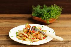 Fried potatoes with scallion and chili in white plate with fork Stock Images