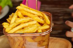 Fried potatoes in a sieve placed on a wooden tray. stock photo