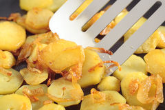 Fried potatoes' slices. The close up view on fried potatoes' slices with addition of chopped onion. In centre of frame the metal kitchen spatula royalty free stock photography