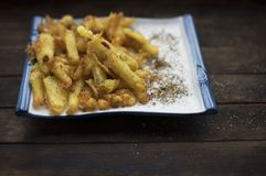 Fried potatoes with spices. French fries fried in vegetable oil and sprinkled with spices royalty free stock image