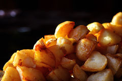 Fried potatoes - street food in India. Fried potatoes on a dark background - street food in India Royalty Free Stock Image
