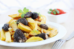 Fried potatoes with thyme. Arugula and mushrooms stock images