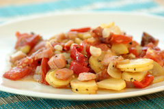 Fried potatoes with tomato as warm salad Royalty Free Stock Images