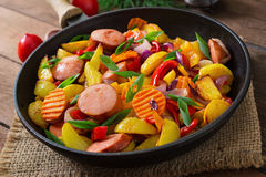 Fried potatoes with vegetables and sausages. Royalty Free Stock Photos