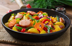 Fried potatoes with vegetables and sausages. Stock Photos