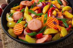 Fried potatoes with vegetables and sausages. Royalty Free Stock Photography