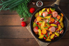 Fried potatoes with vegetables and sausages. Top view Royalty Free Stock Photos