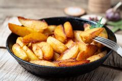 Fried potatoes wedges in a pan stock photos