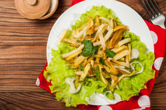 Fried potatoes on a white plate with herbs on wooden background. The view from the top Royalty Free Stock Photos