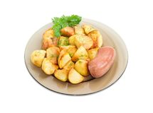 Fried potatoes with wieners on dark glass dish Royalty Free Stock Photos