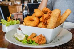 Fried prawn and seafood balls with side salad on wooden table. In restaurant Royalty Free Stock Photography