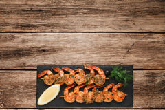 Fried prawns on black slate. Mediterranean food. Appetizing shrimps served on black slate, flat lay. Wooden rustic table background with copy space for text Stock Photo