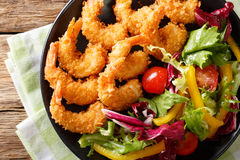 Fried prawns in breadcrumbs and a salad of fresh vegetables clos Royalty Free Stock Photos
