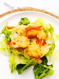 Fried prawns fritters starter. A photograph showing a first course starter dish of some golden brown deepfried prawn fritters served on a fresh raw green salad Royalty Free Stock Photography