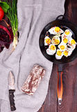 Fried quail eggs in a cast-iron black frying pan. With a wooden handle on the table, next to a whole loaf of rye bread, top view Stock Photo