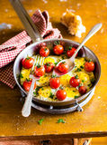 Fried quail eggs with cherry tomatoes, mozzarella cheese and chopped fresh curly parsley in a frying pan for breakfast Royalty Free Stock Photo