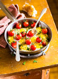 Fried quail eggs with cherry tomatoes, mozzarella cheese and chopped fresh curly parsley in a frying pan for breakfast Royalty Free Stock Photos