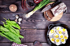 Fried quail eggs in a frying pan,. Near a loaf of rye bread and fresh vegetables, empty space in the middle Royalty Free Stock Photography