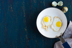 Fried quail eggs on pan, top view Stock Photo