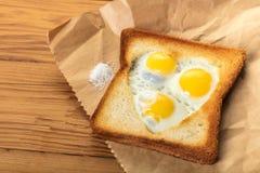Fried quail eggs in a toast Stock Photos