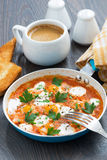 Fried quail eggs in tomato sauce with toasts in a frying pan Royalty Free Stock Photography