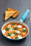 Fried quail eggs in tomato sauce with toasts in a frying pan Stock Photos