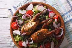 Fried quail and fresh vegetables close-up. horizontal top view. Fried quail and fresh vegetables close-up on the table. horizontal view from above Royalty Free Stock Images