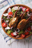 Fried quail and fresh vegetables close-up. vertical top view. Fried quail and fresh vegetables close-up on the table. vertical top view Royalty Free Stock Photography