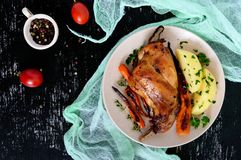 Fried rabbit leg, garnish of boiled potatoes, grilled carrots - on a plate on a dark background. Top view Stock Photo