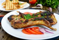 Fried rabbit legs on a white plate on a wooden table. Dietary rabbit meat. Cooked on the grill Stock Photography